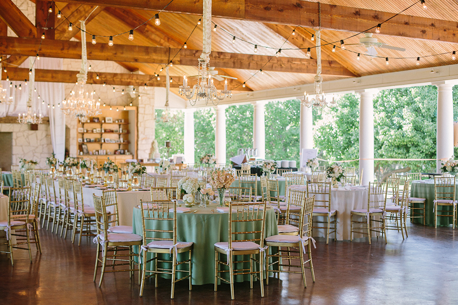 Wedding reception at White Oaks Ranch in Dallas with cafe lights and chandeliers and chiavari chairs