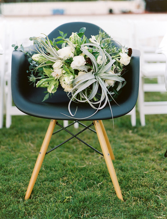Bridal bouquet with an air plant on a black Eames dowel chair