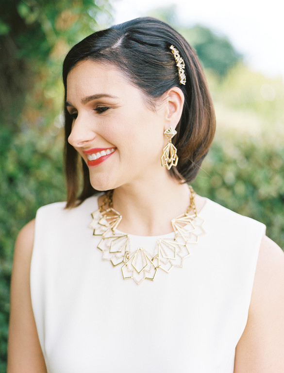 Wedding day bridal portrait featuring gold necklace, hair clip, and earrings