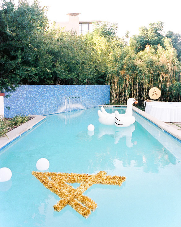 Inflatable swan and floating lights in pool used for wedding decor