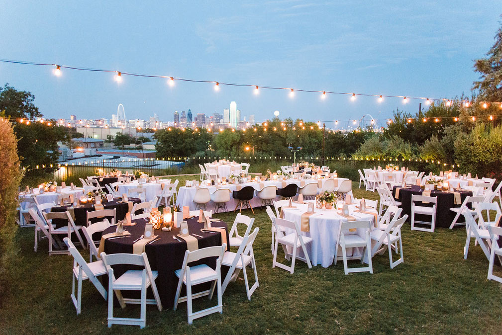 Tables and cafe lights at wedding reception at The Belmont Hotel overlooking downtown Dallas