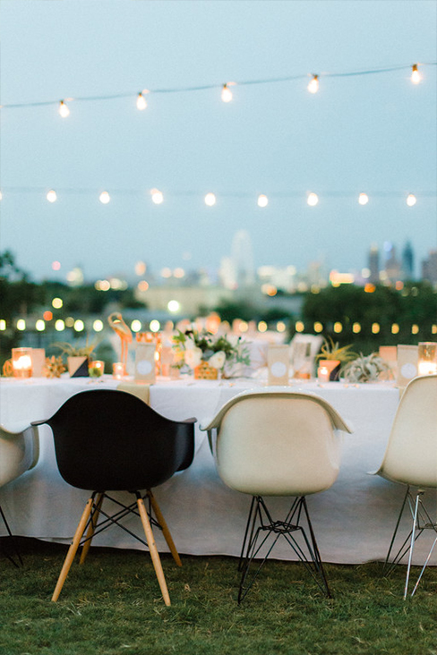 Black and white Eames molded plastic chairs and cafe lights at wedding reception overlooking downtown Dallas