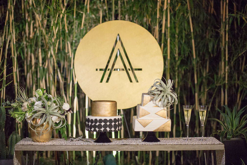 Black, white, and gold dot and triangle shape wedding cakes with custom laser cut wood circle monogram sign at The Hotel Belmont