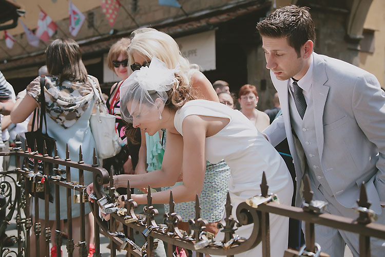 Bride and Groom Placing Padlock on Ponte Vecchio Gate