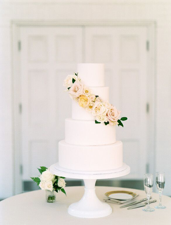 4 tier faux wedding cake with peach and blush blooms