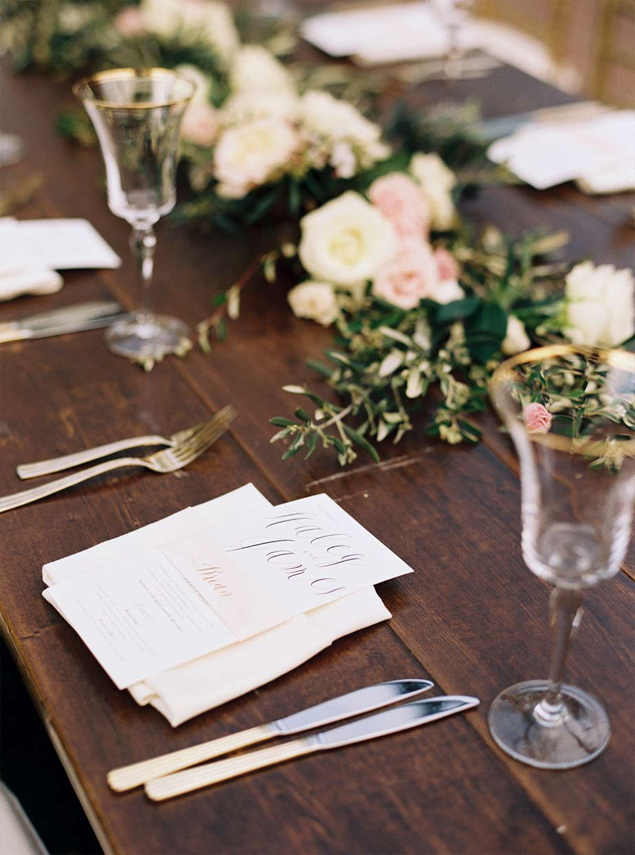 Wooden reception head table wedding place setting with gold rimmed glasses and floral garland