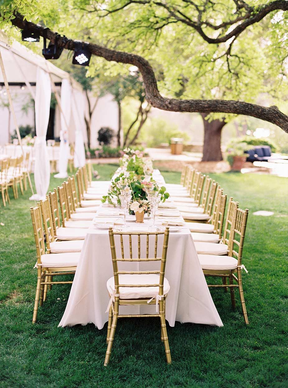 Long wedding reception table setup with gold chiavari chairs at The Degolyer House at The Dallas Arboretum