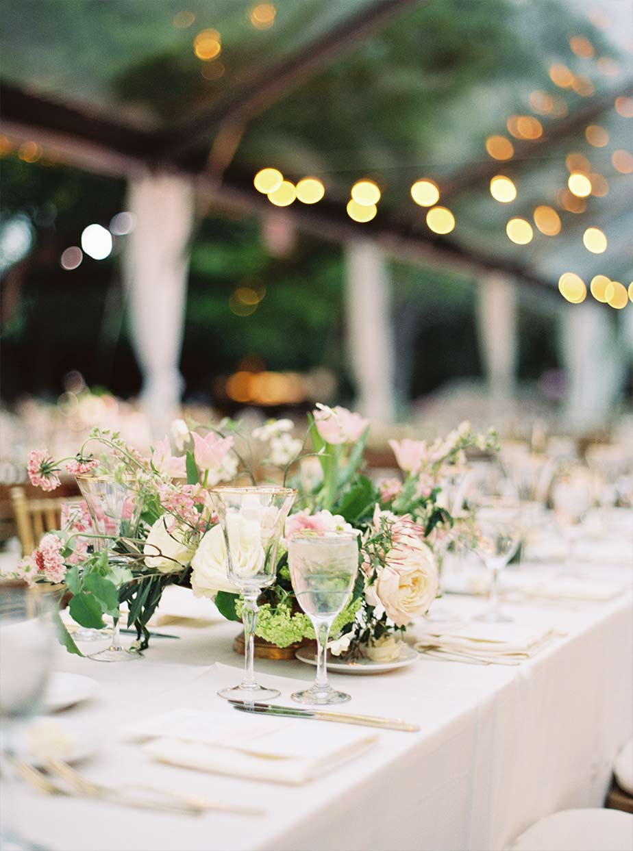 Long wedding reception table detail with cafe lighting and clear tent