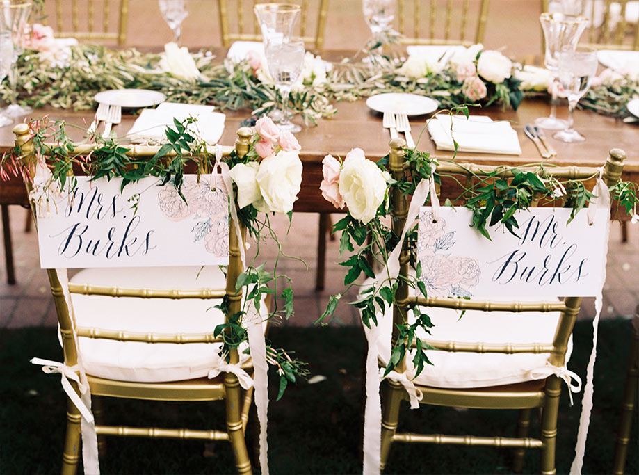 Wooden wedding reception head table with bride and groom calligraphy signs on gold chiavari chairs