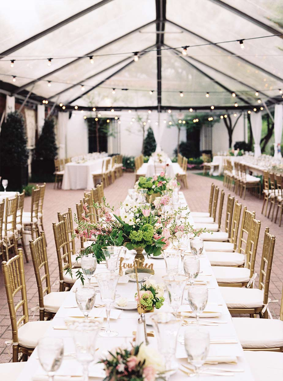Long wedding reception table detail with cafe lighting and clear tent at The Degolyer House at The Dallas Arboretum