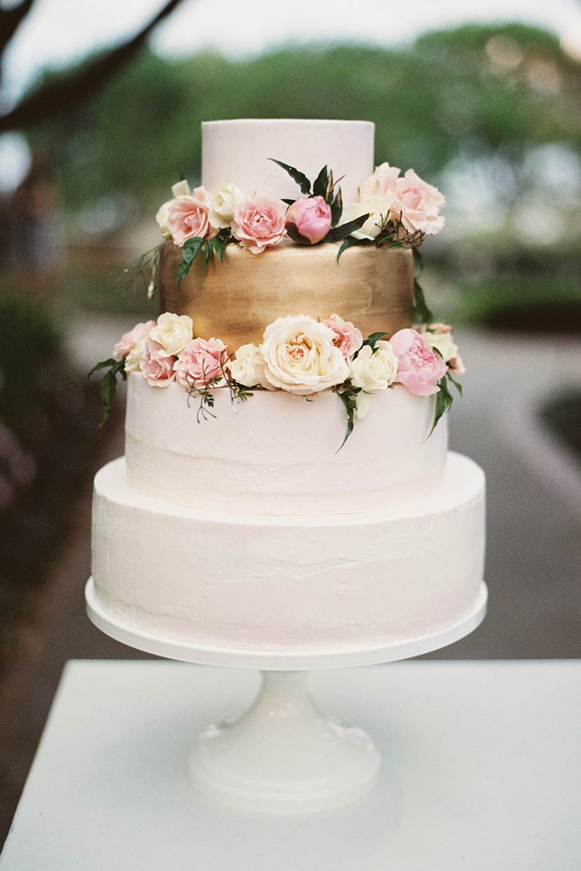 White and gold buttercream wedding bridal cake with fresh flowers