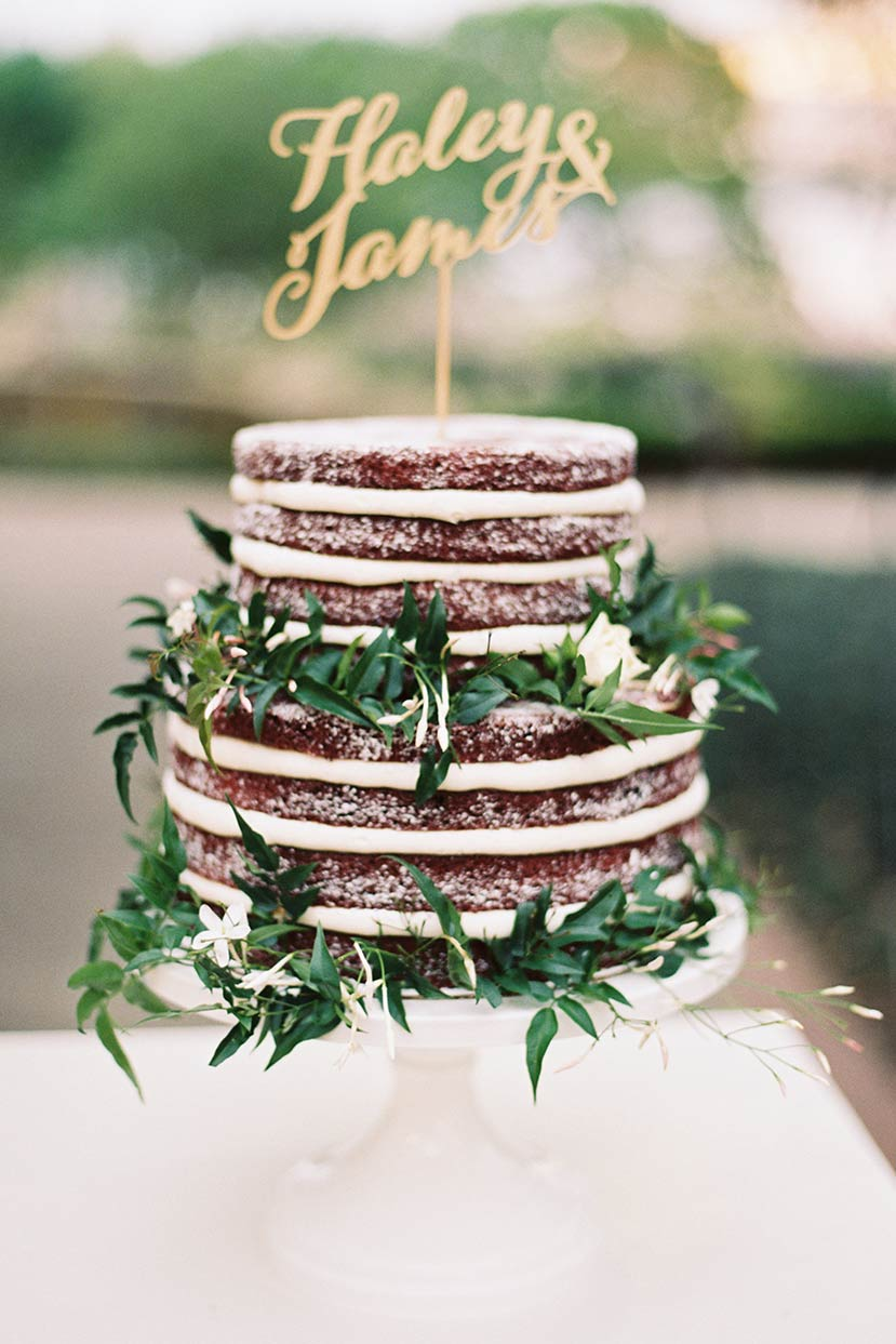 Naked wedding cake with floral greenery decor and gold laser cut topper