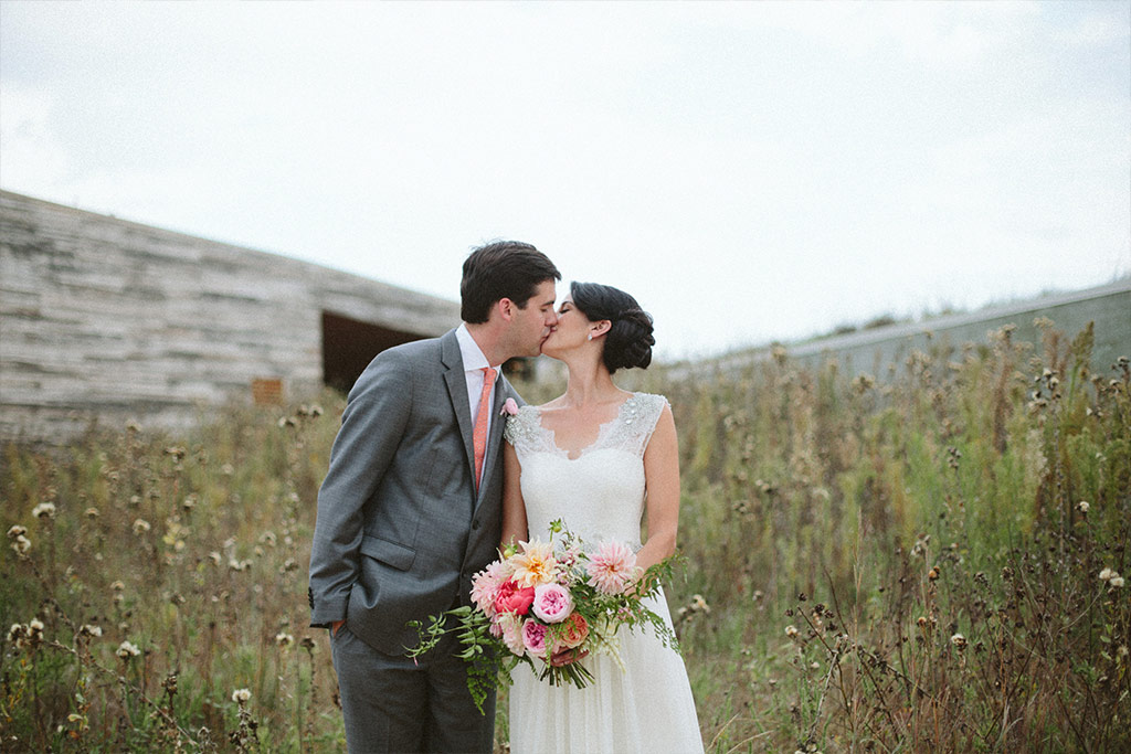 Bride and groom kiss for a wedding day portrait in front of Trinity River Audubon Center in Dallas