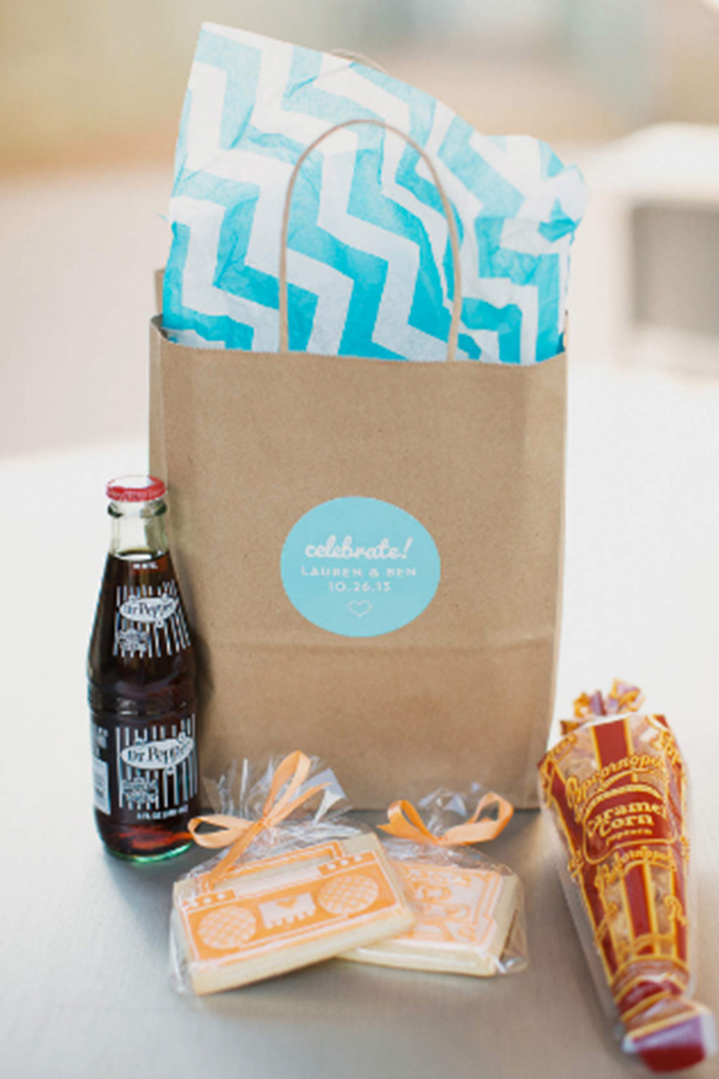 Dr. Pepper, popcorn, and tape cassette cookies in wedding out of town welcome hotel bag