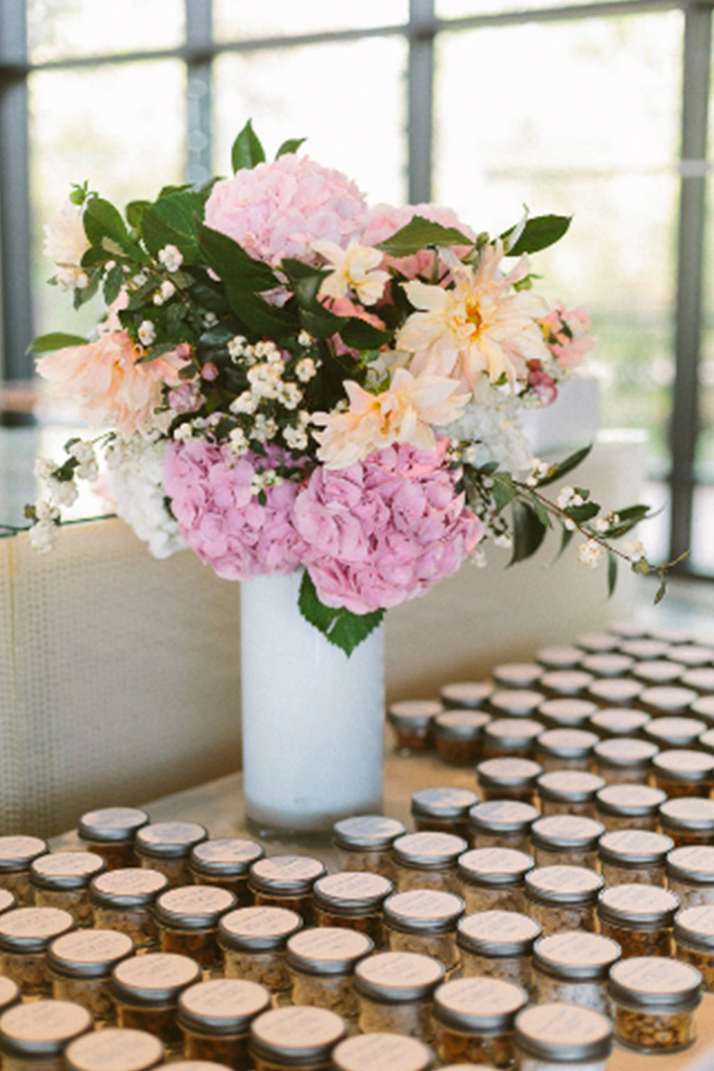 Cookie jar wedding escort card setup with pink and peach floral