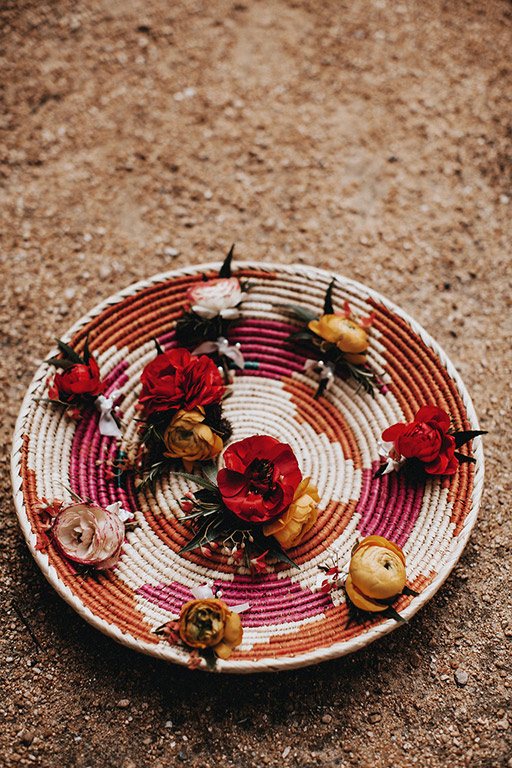 Ranunculus boutonnieres in a woven bowl for the groomsmen