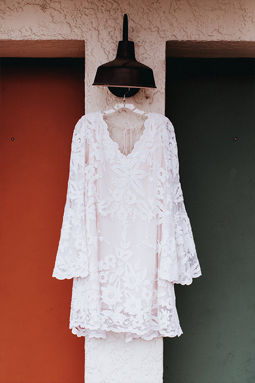 Bride's short, belle long sleeve, lace, custom Patti Flowers wedding dress hanging in front of The Belmont Hotel room