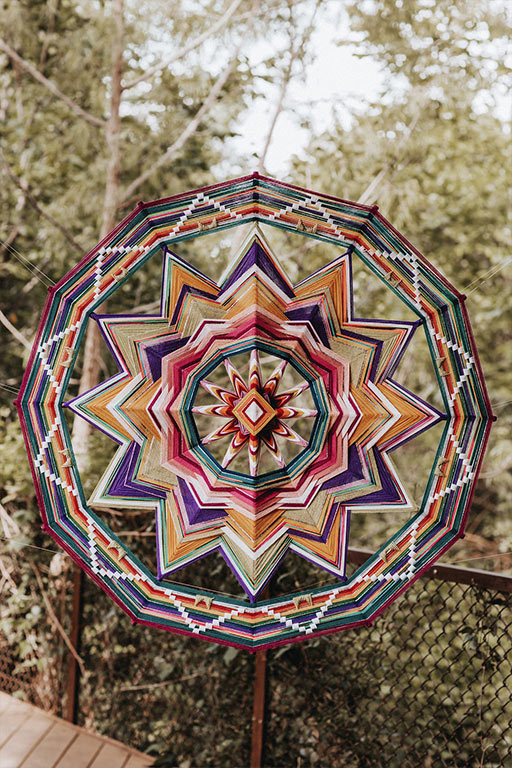 A colorful, giant ojo de Dios or eye of God, by Jay the Weaver, used as a wedding altar decoration