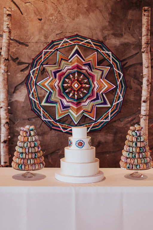 The wedding cake and macaroon towers, with a colorful, giant ojo de Dios or eye of God backdrop by Jay the Weaver