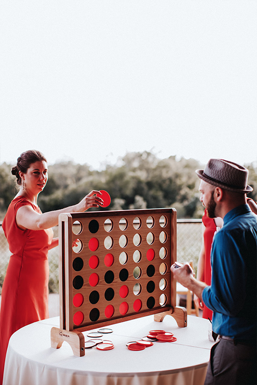 A giant wooden connect four game being played by wedding guests at the reception