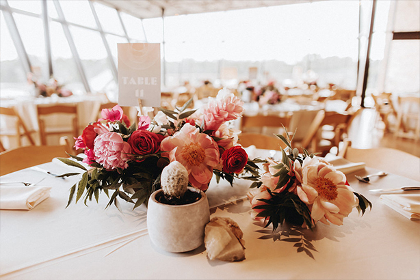 A collection of wedding reception centerpieces with geodes and concrete vessels at the Trinity River Audubon Center in Dallas
