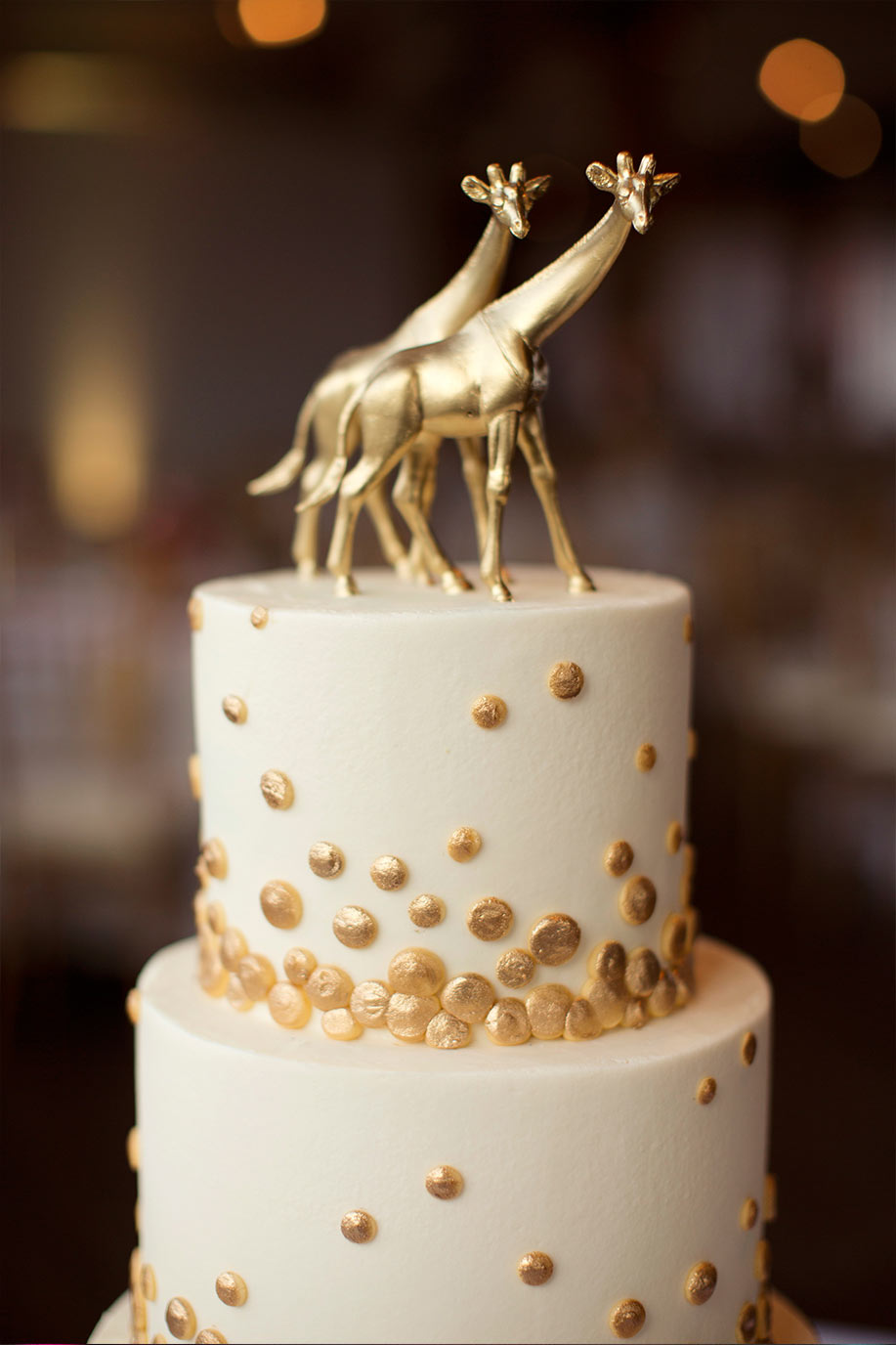Brides wedding cake with gold polka dots and giraffe topper