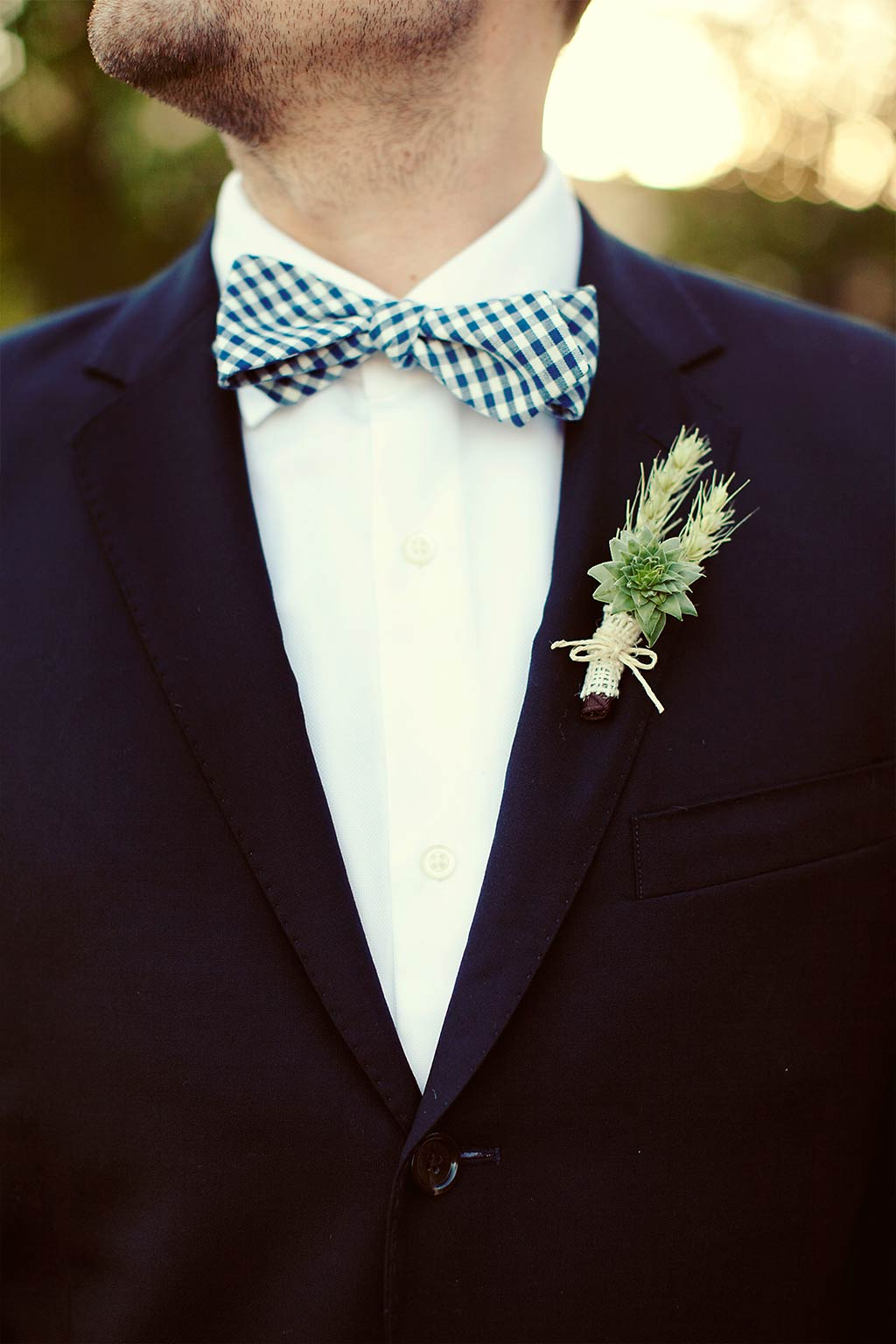 succulent and wheat grooms boutonniere with checkered bowtie