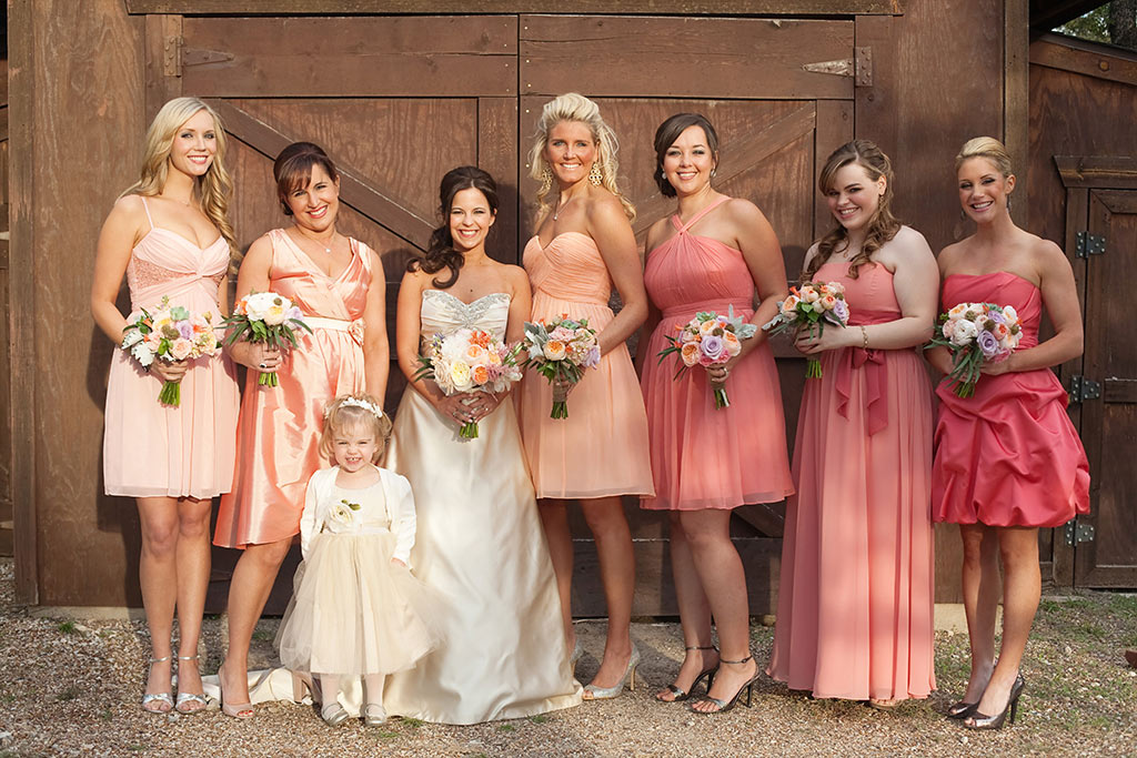 peach mix and match bridesmaids dresses in front of barn