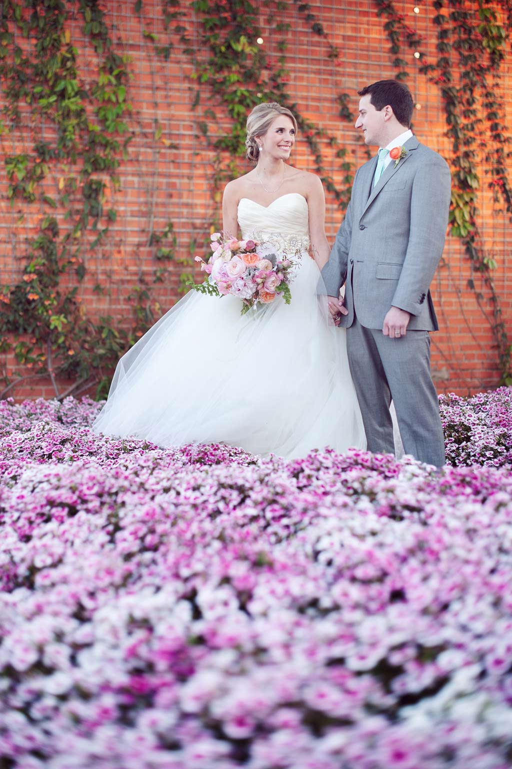Bridge and groom portrait over purple flower field at Hickory Street Annex in Dallas