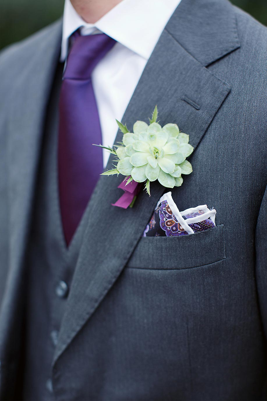 Groom's succulent boutonniere with purple tie and gray suit