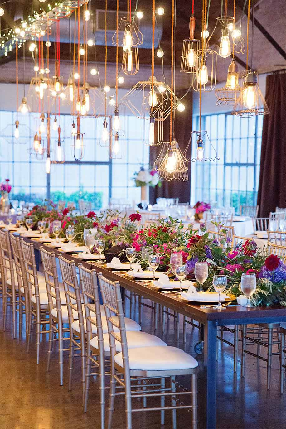 Wedding long head table with pink and purple floral garland and industrial cage lights at Hickory Street Annex in Dallas