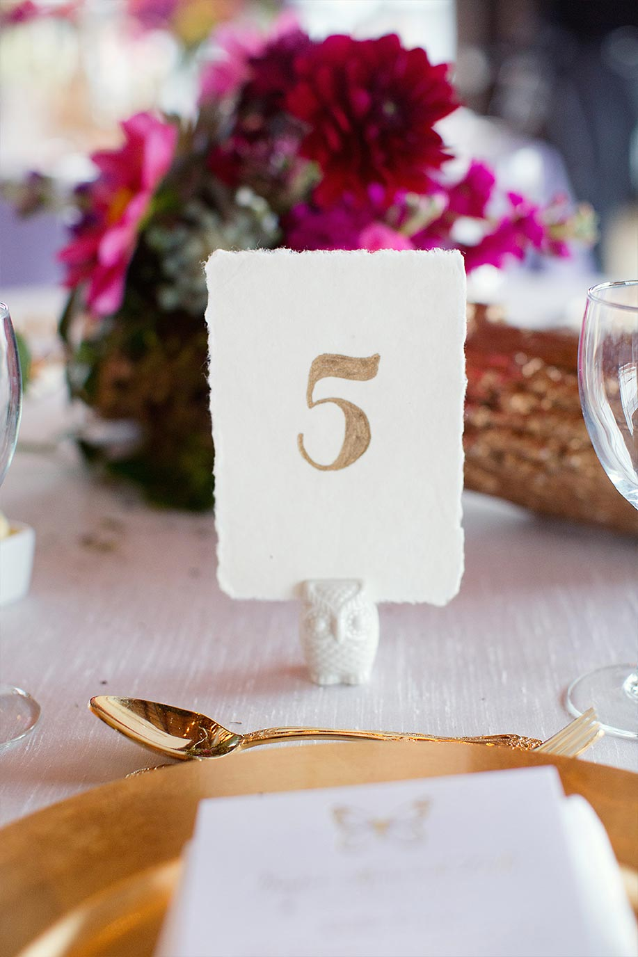 Gold calligraphy table number on deckle edge paper